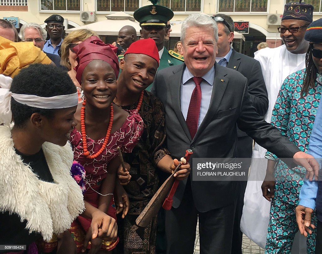 German President Joachim Gauck dances with a cultural troupe at the Freedom Park in Lagos, on February 9, 2016. Gauck, accompanied by his wife and top government functionaries as well as strong delegation from the business community, is in Nigeria to strengthen cooperation between the two countries. / AFP / FLORIAN PLAUCHEUR
