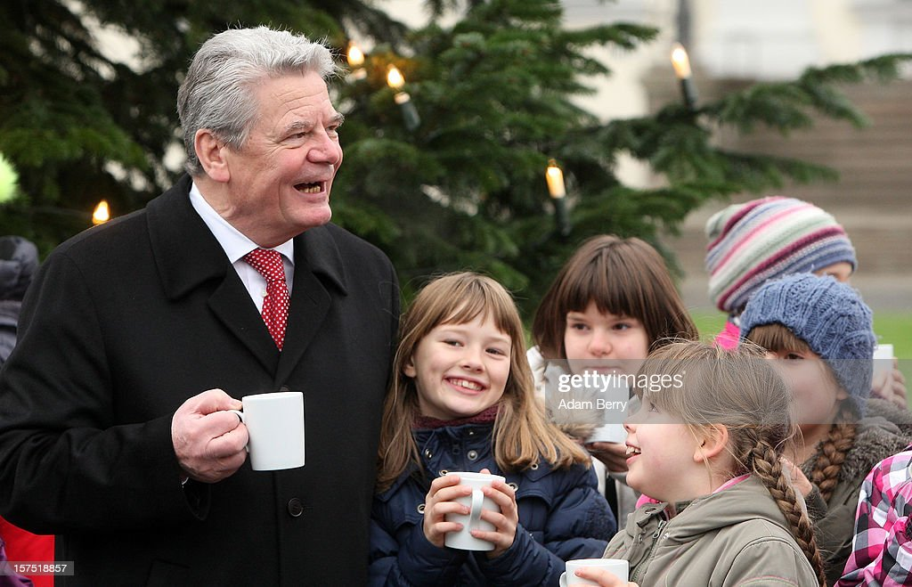 German President Joachim Gauck drinks mulled punch as he speaks to students of the Carl von Ossietzky school during the illumination ceremony for the Christmas tree at Bellevue Presidential Palace on December 4, 2012 in Berlin, Germany. The 12-meter (40-foot) tall Colorado blue spruce (Picea pungens) was planted in 1994 and is being supplied to the president for the second time by Werderaner Tannenhof Christmas tree farm in the town of Werder, just outside of the German capital.