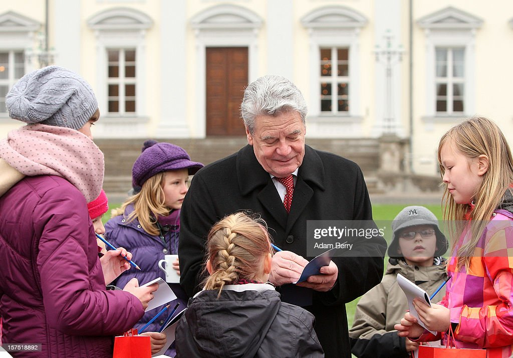 German President Joachim Gauck (C) gives autographs to students of the Carl von Ossietzky school during the illumination ceremony for the Christmas tree at Bellevue Presidential Palace on December 4, 2012 in Berlin, Germany. The 12-meter (40-foot) tall Colorado blue spruce (Picea pungens) was planted in 1994 and is being supplied to the president for the second time by Werderaner Tannenhof Christmas tree farm in the town of Werder, just outside of the German capital.