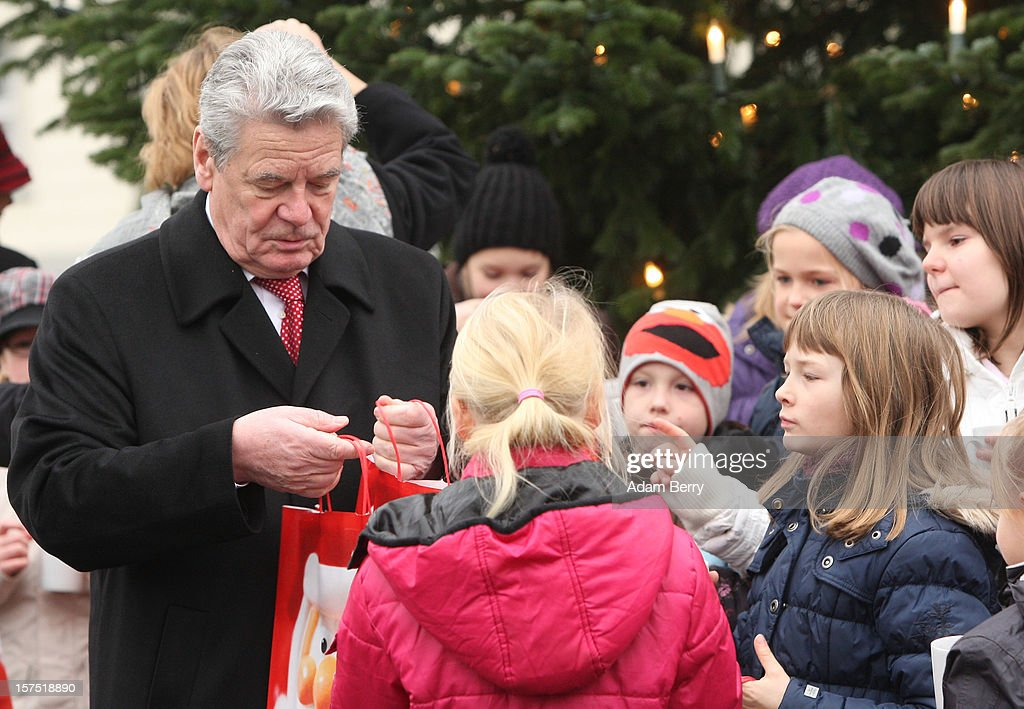 German President Joachim Gauck (C) gives gift bags to students of the Carl von Ossietzky school during the illumination ceremony for the Christmas tree at Bellevue Presidential Palace on December 4, 2012 in Berlin, Germany. The 12-meter (40-foot) tall Colorado blue spruce (Picea pungens) was planted in 1994 and is being supplied to the president for the second time by Werderaner Tannenhof Christmas tree farm in the town of Werder, just outside of the German capital.