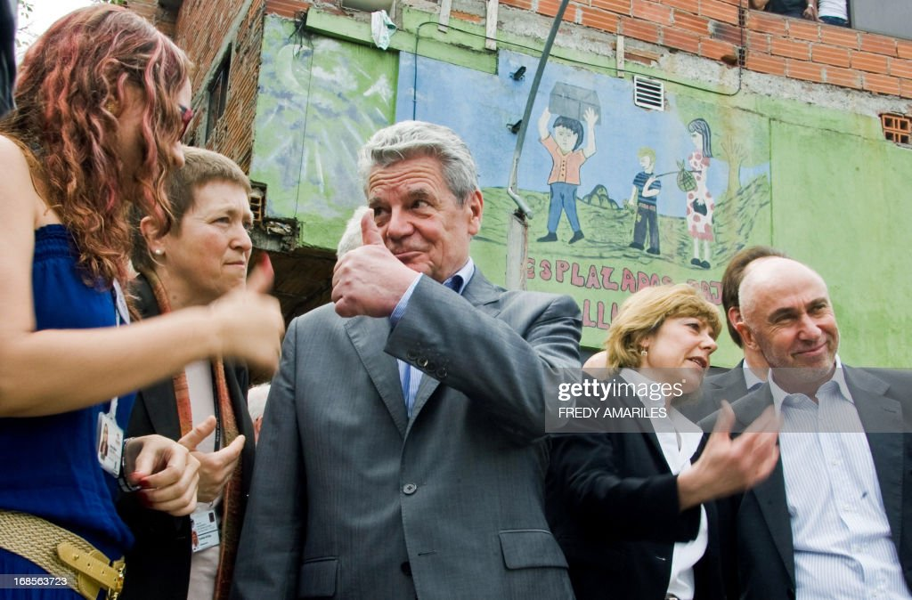 German President Joachim Gauck (C) gives his thumb up during a visit to the northeastern commune of Medellin, Colombia, on May 11, 2013. Gauck is in Colombia in a four-day official visit, part of a Latin American tour. AFP PHOTO / Fredy Amariles
