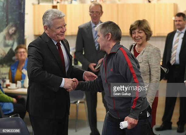 German President Joachim Gauck greets soup kitchen regular visitor Silvya Mortelock as First Lady Daniela Schadt looks on while the two visited the...
