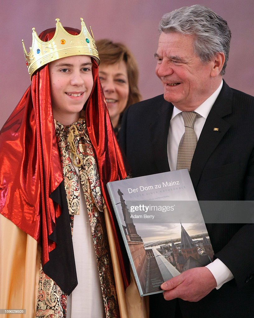 German President Joachim Gauck holds a book presented him by child Epiphany carolers, known as Sternsinger in German, during their visit to Bellevue presidential palace on January 6, 2013 in Berlin, Germany. The children walk from house to house in the days around January 6, singing carols and collecting money for needy children around the world, dressed as the Three Magi of the Christmas story in the Gospel of Matthew.