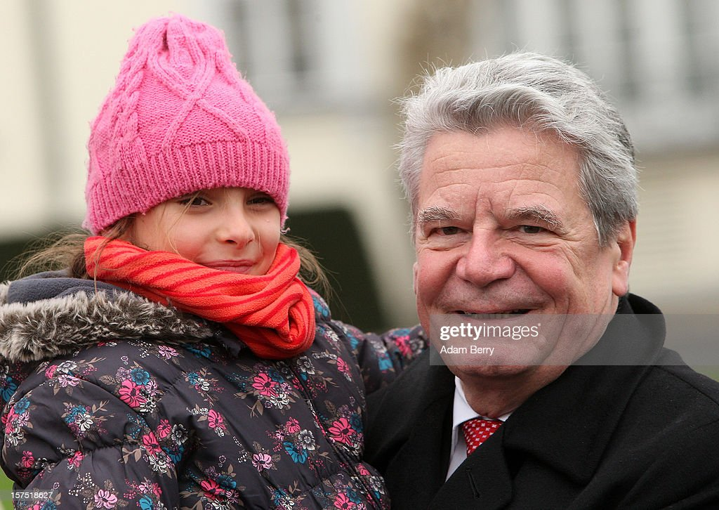 German President <a gi-track='captionPersonalityLinkClicked' href=/galleries/search?phrase=Joachim+Gauck&family=editorial&specificpeople=2077888 ng-click='$event.stopPropagation()'>Joachim Gauck</a> holds a child from the Carl von Ossietzky school during the illumination ceremony for the Christmas tree at Bellevue Presidential Palace on December 4, 2012 in Berlin, Germany. The 12-meter (40-foot) tall Colorado blue spruce (Picea pungens) was planted in 1994 and is being supplied to the president for the second time by Werderaner Tannenhof Christmas tree farm in the town of Werder, just outside of the German capital.