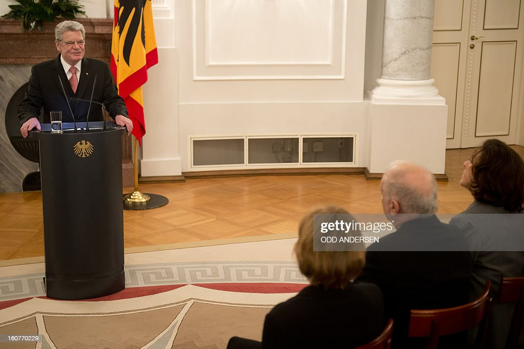 German President Joachim Gauck (L) holds the honorific speech to Argentinian-born conductor Daniel Barenboim (2nd R) on behalf of his awarding with the German order of Merit for services to music and culture before a dinner in his honour at the Bellevue Palace in Berlin on February 5, 2013.