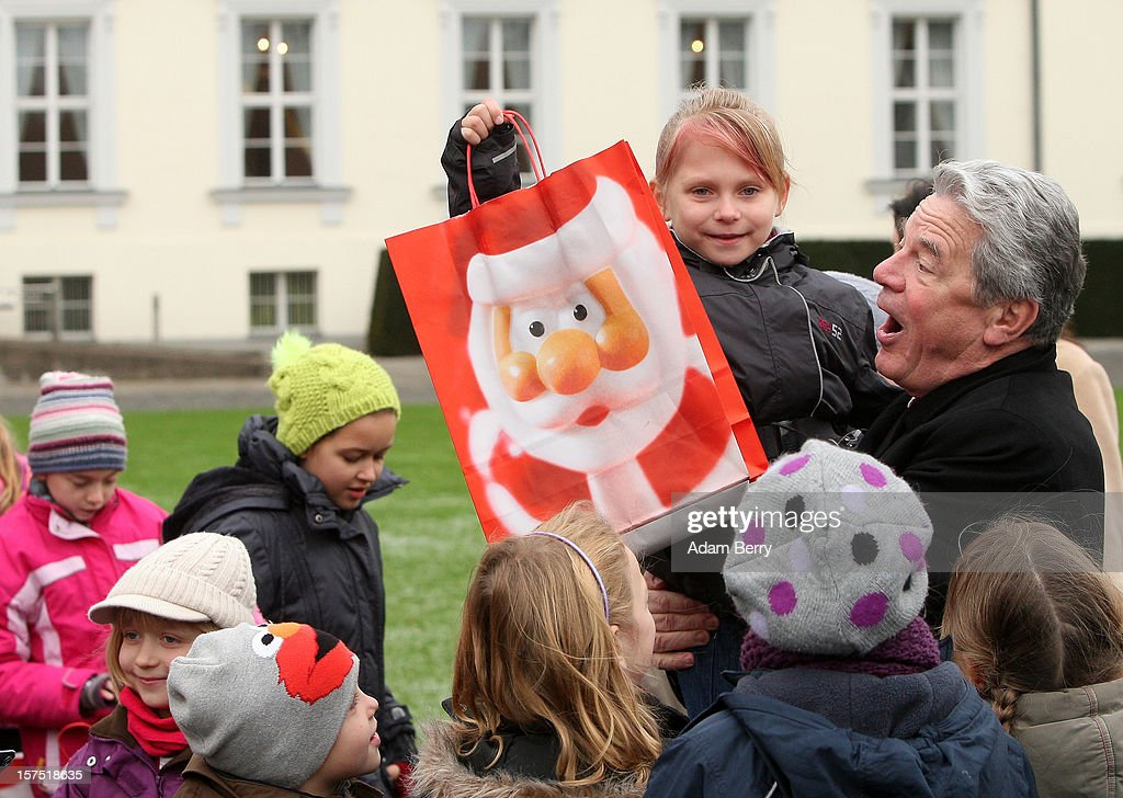 German President <a gi-track='captionPersonalityLinkClicked' href=/galleries/search?phrase=Joachim+Gauck&family=editorial&specificpeople=2077888 ng-click='$event.stopPropagation()'>Joachim Gauck</a> hugs a child from the Carl von Ossietzky school holding a gift bag during the illumination ceremony for the Christmas tree at Bellevue Presidential Palace on December 4, 2012 in Berlin, Germany. The 12-meter (40-foot) tall Colorado blue spruce (Picea pungens) was planted in 1994 and is being supplied to the president for the second time by Werderaner Tannenhof Christmas tree farm in the town of Werder, just outside of the German capital.