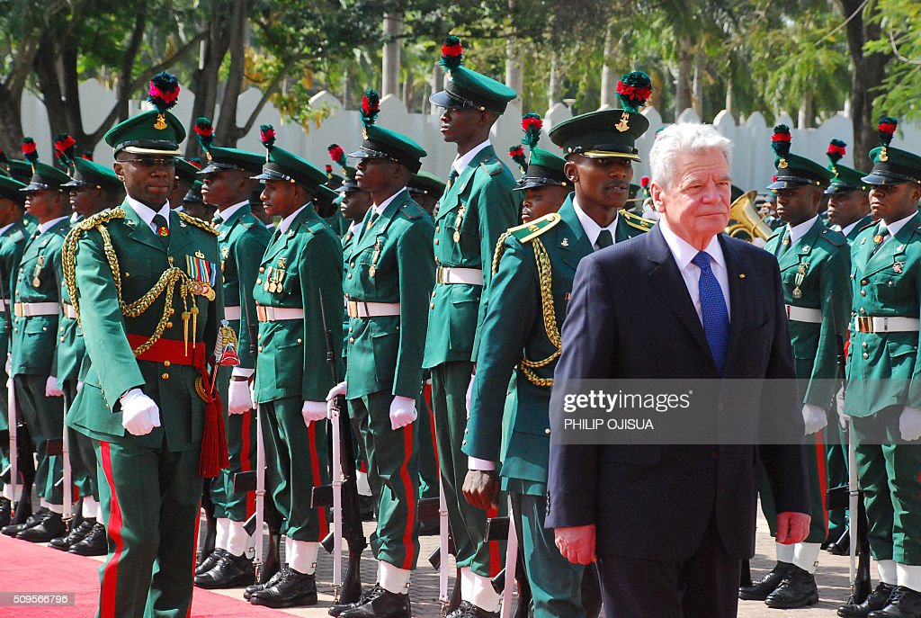 German President Joachim Gauck inspects a military guard of honour during a ceremonial reception at the presidential palace in Abuja, on February 11, 2016. Gauck, accompanied by his partner and top government functionaries as well as strong delegation from the business community, is in Nigeria to strengthen cooperation between the two countries. / AFP / PHILIP OJISUA