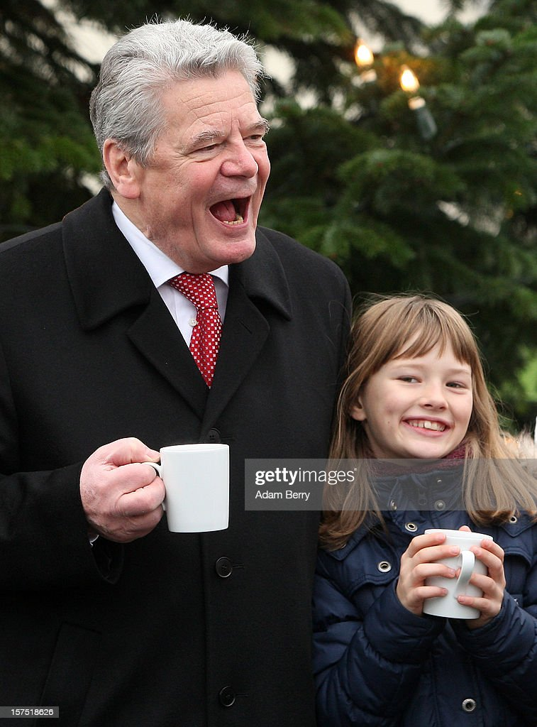 German President <a gi-track='captionPersonalityLinkClicked' href=/galleries/search?phrase=Joachim+Gauck&family=editorial&specificpeople=2077888 ng-click='$event.stopPropagation()'>Joachim Gauck</a> laughs with a child from the Carl von Ossietzky school while drinking mulled punch during the illumination ceremony for the Christmas tree at Bellevue Presidential Palace on December 4, 2012 in Berlin, Germany. The 12-meter (40-foot) tall Colorado blue spruce (Picea pungens) was planted in 1994 and is being supplied to the president for the second time by Werderaner Tannenhof Christmas tree farm in the town of Werder, just outside of the German capital.