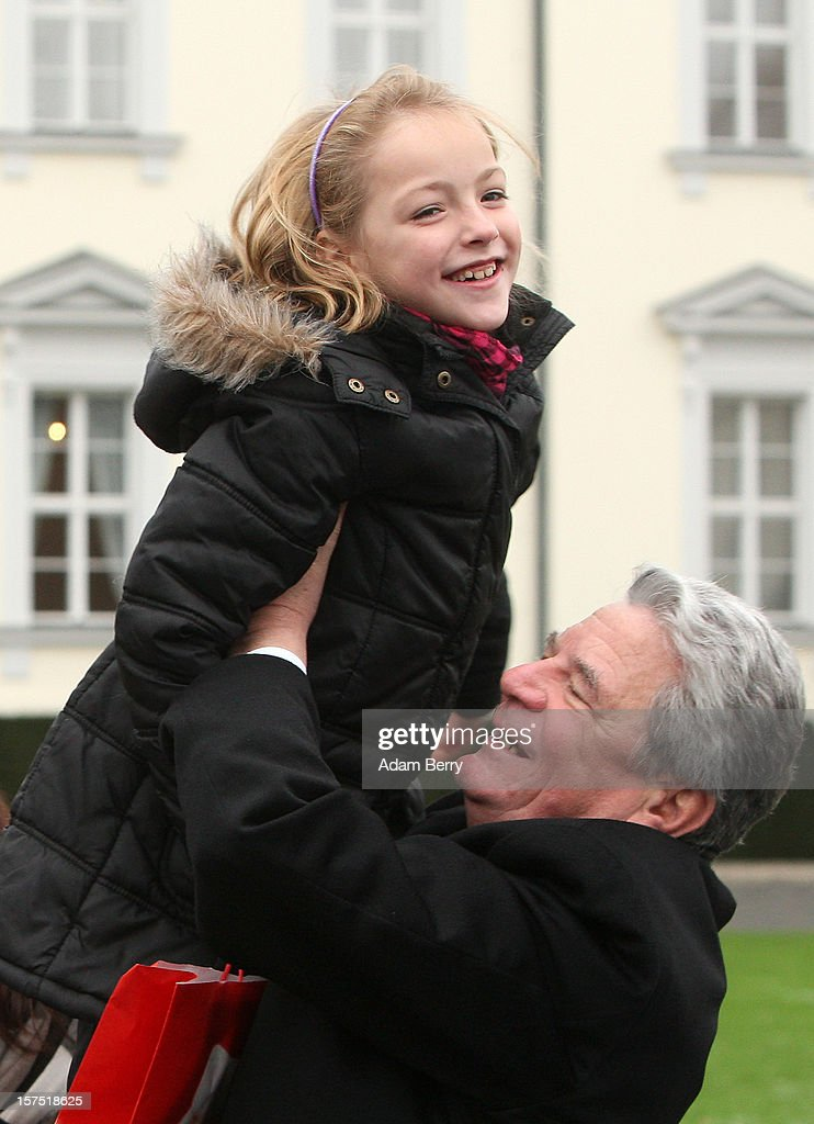 German President <a gi-track='captionPersonalityLinkClicked' href=/galleries/search?phrase=Joachim+Gauck&family=editorial&specificpeople=2077888 ng-click='$event.stopPropagation()'>Joachim Gauck</a> lifts a child from the Carl von Ossietzky school during the illumination ceremony for the Christmas tree at Bellevue Presidential Palace on December 4, 2012 in Berlin, Germany. The 12-meter (40-foot) tall Colorado blue spruce (Picea pungens) was planted in 1994 and is being supplied to the president for the second time by Werderaner Tannenhof Christmas tree farm in the town of Werder, just outside of the German capital.