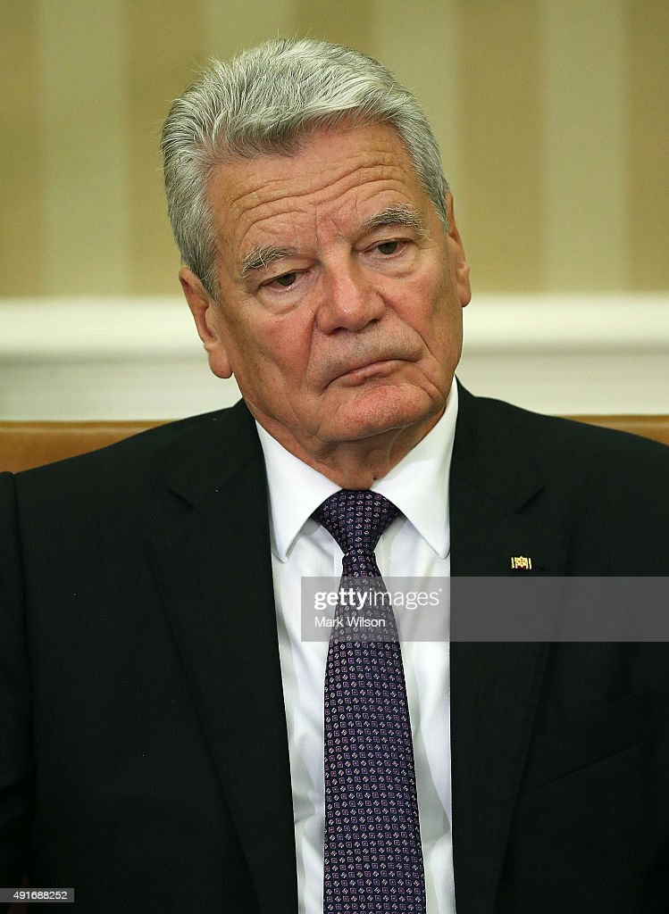 German President Joachim Gauck listens to US President Barack Obama speak to the media during a meeting in the Oval Office at the White House October 7, 2015 in Washington, DC. The two leaders participated in a bi lateral meeting that marked theÊ25th anniversary of German reunification