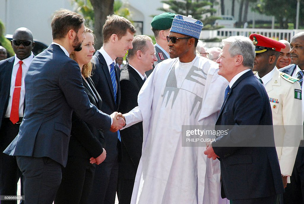 German President Joachim Gauck (L) looks as Nigeria's President Muhammadu Buhari (2ndL) shakes hand with members of German delegation during a ceremonial reception at the presidential palace in Abuja, on February 11, 2016. Gauck, accompanied by his partner and top government functionaries as well as strong delegation from the business community, is in Nigeria to strengthen cooperation between the two countries. / AFP / PHILIP OJISUA