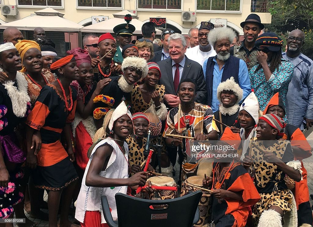 German President Joachim Gauck (C, up), next to his wife Gerhild and playwright Professor Wole Soyinka, poses with a cultural troupe at the Freedom Park in Lagos, on February 9, 2016. Gauck, accompanied by his wife and top government functionaries as well as strong delegation from the business community, is in Nigeria to strengthen cooperation between the two countries. / AFP / FLORIAN PLAUCHEUR
