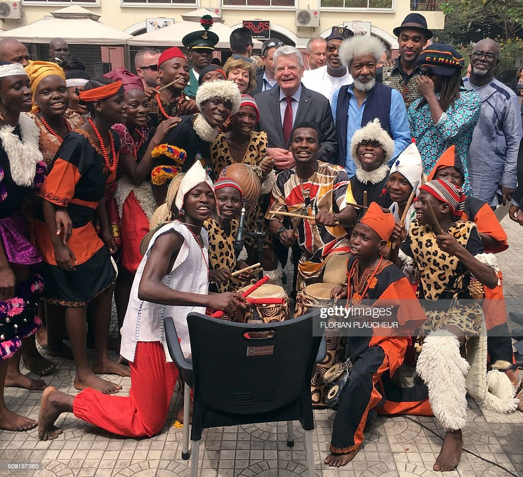German President Joachim Gauck (C), next to his wife Gerhild and playwright Professor Wole Soyinka, poses with a cultural troupe at the Freedom Park in Lagos, on February 9, 2016. Gauck, accompanied by his wife and top government functionaries as well as strong delegation from the business community, is in Nigeria to strengthen cooperation between the two countries. / AFP / FLORIAN PLAUCHEUR