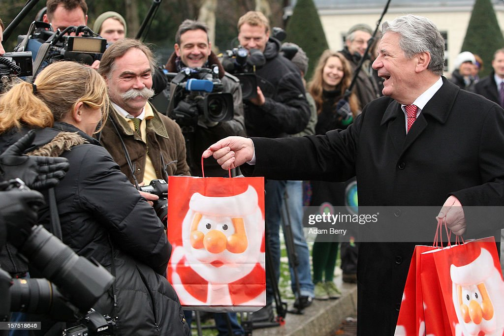 German President <a gi-track='captionPersonalityLinkClicked' href=/galleries/search?phrase=Joachim+Gauck&family=editorial&specificpeople=2077888 ng-click='$event.stopPropagation()'>Joachim Gauck</a> (R) offers a gift bag to photographers during the illumination ceremony for the Christmas tree at Bellevue Presidential Palace on December 4, 2012 in Berlin, Germany. The 12-meter (40-foot) tall Colorado blue spruce (Picea pungens) was planted in 1994 and is being supplied to the president for the second time by Werderaner Tannenhof Christmas tree farm in the town of Werder, just outside of the German capital.