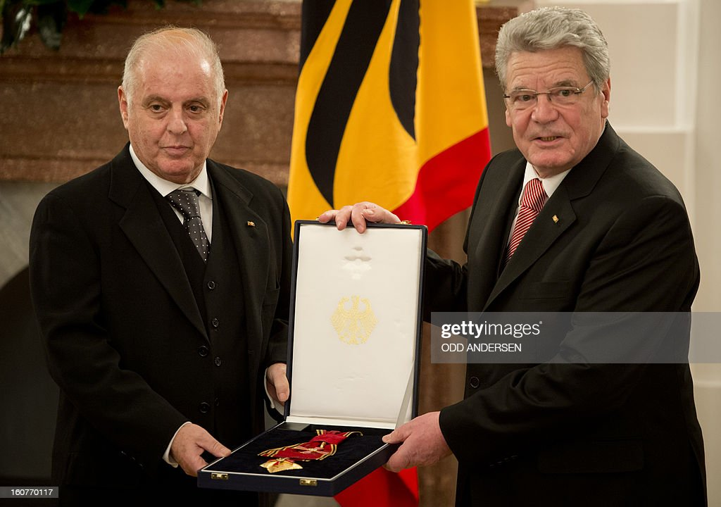 German President Joachim Gauck (R) presents Argentinian-born conductor Daniel Barenboim the German Order of Merit for services to music and culture before a dinner in his honour at the Bellevue Palace in Berlin on February 5, 2013.