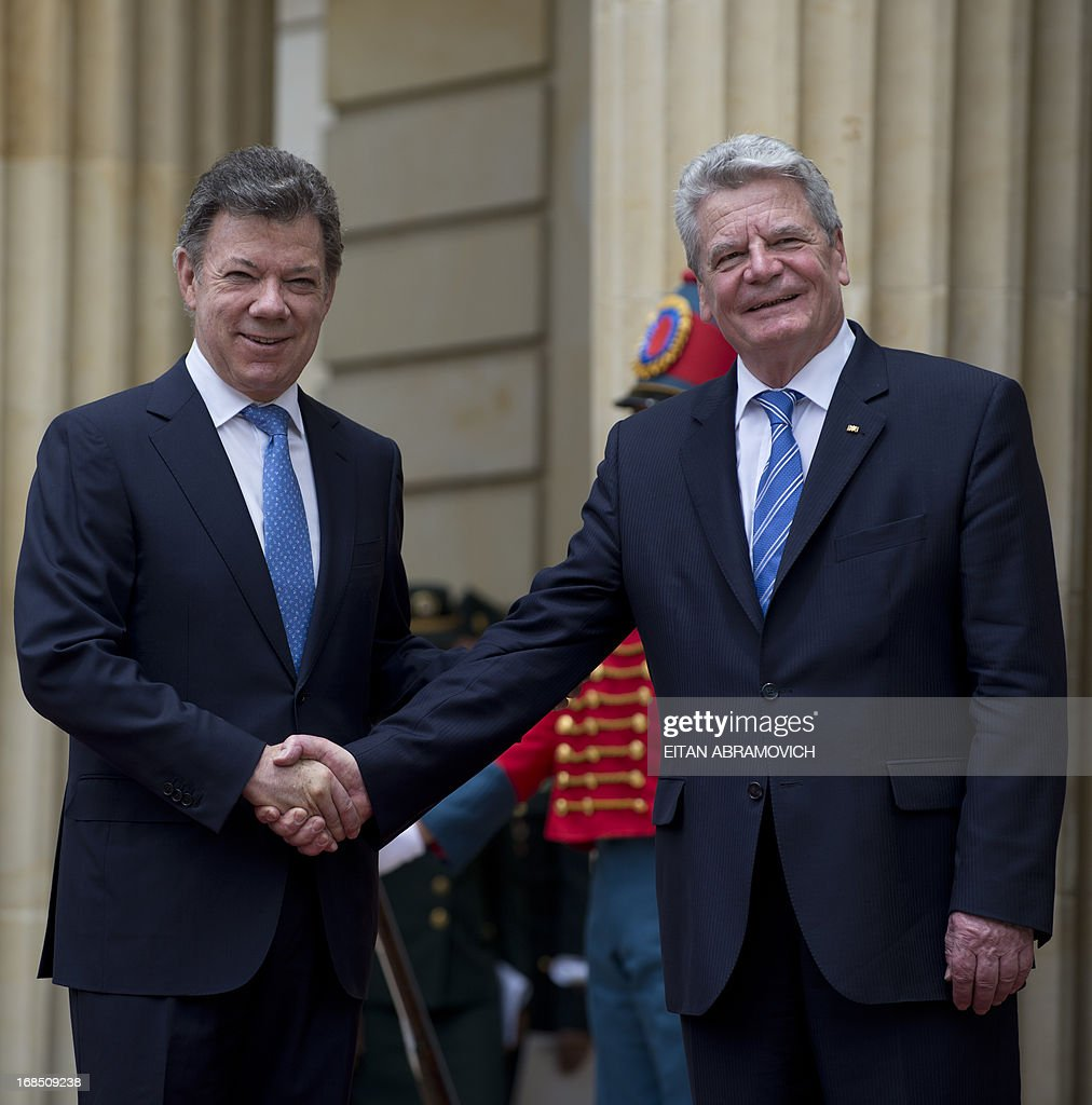 German President Joachim Gauck (R) shakes hands with his Colombian counterpart Juan Manuel Santos during a welcoming ceremony at Narino Presidential Palace in Bogota, Colombia, on May 10, 2013. Gauck is on a four-day official visit to Colombia. AFP PHOTO/Eitan Abramovich