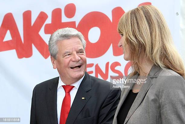 German President Joachim Gauck speaks to an employee of the Aktion Mensch organization to benefit handicapped children at the Citizens Fest at...