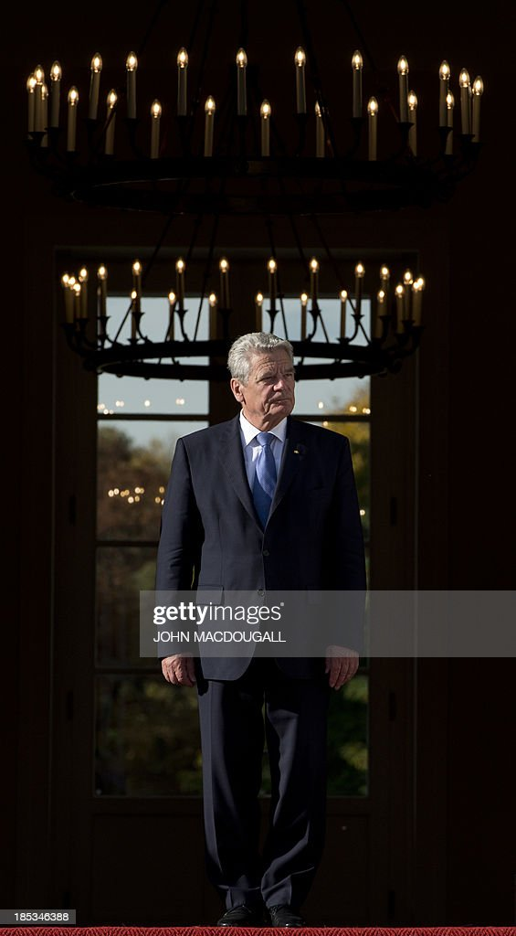 German President Joachim Gauck steps out of the presidential palace to greet President of the Palestinian National Authority for talks at the presidential palace in Berlin October 19, 2013. Mahmud Abbas actually tours Europe. AFP PHOTO / JOHN MACDOUGALL