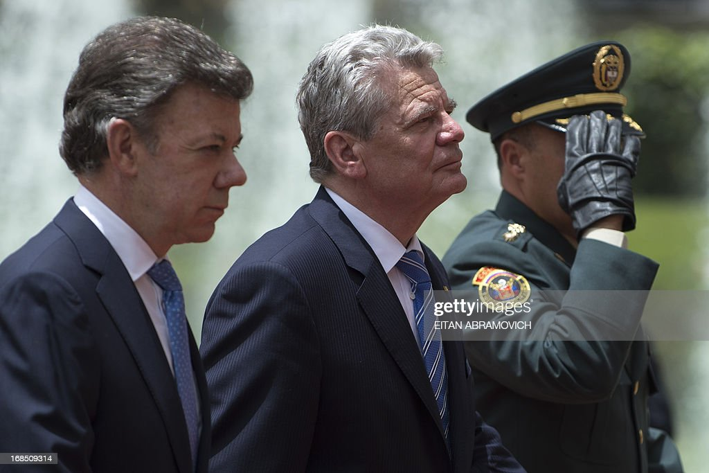 German President Joachim Gauck (C) walks next to his Colombian counterpart Juan Manuel Santos during a welcoming ceremony at Narino Presidential Palace in Bogota, Colombia, on May 10, 2013. Gauck is on a four-day official visit to Colombia. AFP PHOTO/Eitan Abramovich
