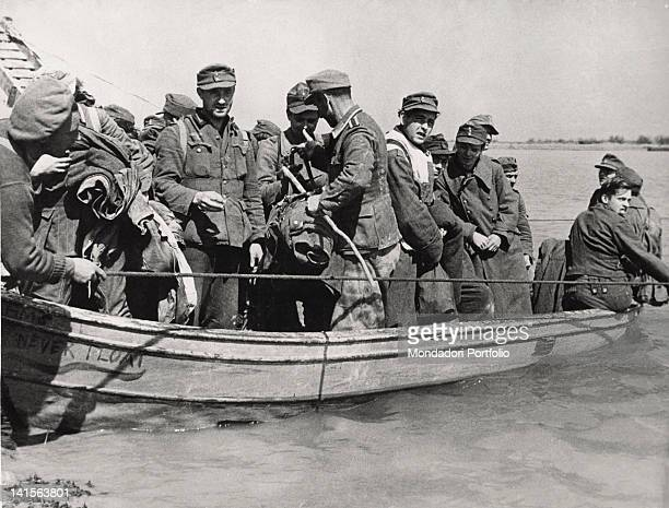 German prisoners taken by the Eighth Army of the Allied Forces during the 2nd April British offensive on Comacchio wetlands are ferried on a boat...
