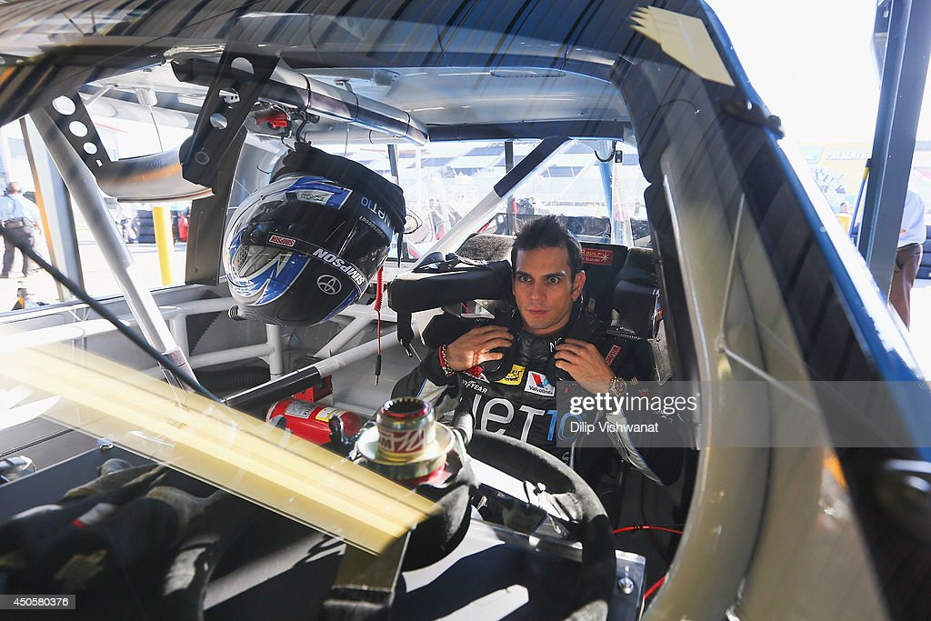 German Quiroga, driver of the #77 Net 10 Wireless Toyota straps himself into his truck prior to practice for the NASCAR Camping World Truck Series Drivin' for Linemen 200 at Gateway Motorsports Park on June 13, 2014 in Madison, Illinois.