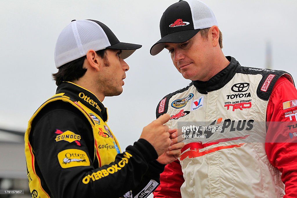 German Quiroga, driver of the #77 OtterBox Toyota, talks with Timothy Peters, driver of the #17 Parts Plus Toyota, during qualifying for the NASCAR Camping World Truck Series Chevrolet Silverado 250 at Canadian Tire Motorsport Park on August 31, 2013 in Bowmanville, Canada.