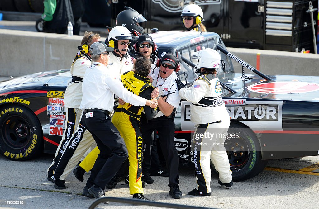 German Quiroga, of Mexico driver of the #77 OtterBox Toyota, is restrained by NASCAR officials as he tries to get to <a gi-track='captionPersonalityLinkClicked' href=/galleries/search?phrase=James+Buescher&family=editorial&specificpeople=5409134 ng-click='$event.stopPropagation()'>James Buescher</a>, driver of the #31 Motomaster Eliminator Chevrolet after the NASCAR Camping World Truck Series Chevrolet Silverado 250 at the Canadian Tire Motorsports Park on September 1, 2013 in Bowmanville, Ontario, Canada.