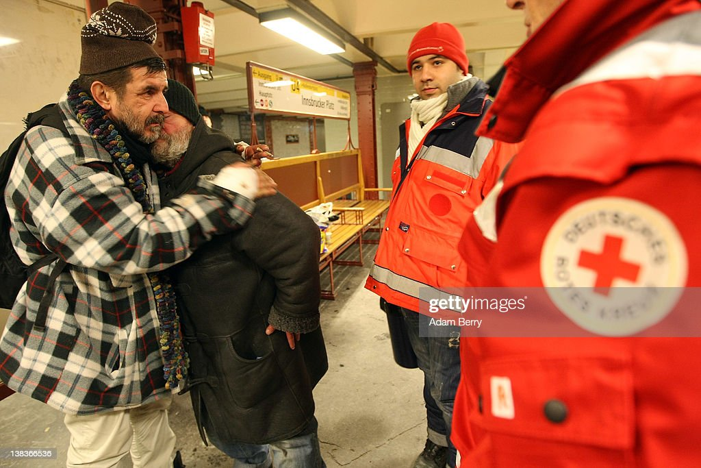 German Red Cross volunteer Adel Far (C) stands next to fellow volunteer Carlo Trobisch as two homeless men hug each other in the Innsbrucker Platz subway station as Far and Trobisch make the rounds in the Waermebus, or Warmth Van, on February 6, 2012 in Berlin, Germany. The Waermebus, a program ran by the German Red Cross, assists the homeless in times of extremely low temperatures with blankets, food, clothing and finding lodging. Nearly 300 people across Europe have died during the current cold wave, a majority of whom were without shelter.