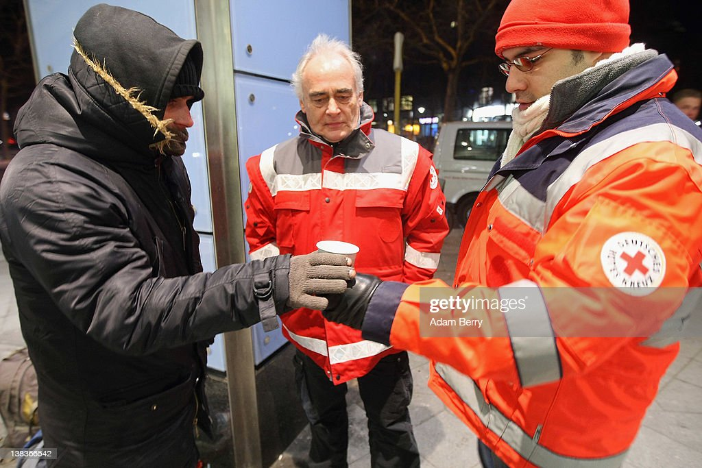 German Red Cross volunteers Adel Far (R) and Carlo Trobisch (C) give a cup of tea to a homeless man by the name of Steve outside of a grocery store as they make the rounds in the Waermebus, or Warmth Van, on February 6, 2012 in Berlin, Germany. The Waermebus, a program ran by the German Red Cross, assists the homeless in times of extremely low temperatures with blankets, food, clothing and finding lodging. Nearly 300 people across Europe have died during the current cold wave, a majority of whom were without shelter.