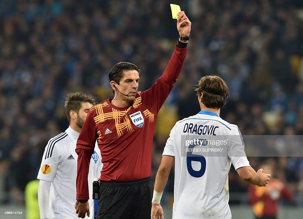 German referee Deniz Aytekin shows a yellow card to Dynamo Kiev's Aleksandar Dragovic during the UEFA Europa League round of 16 football match between Dynamo Kiev and Everton in Kiev on March 19, 2015.