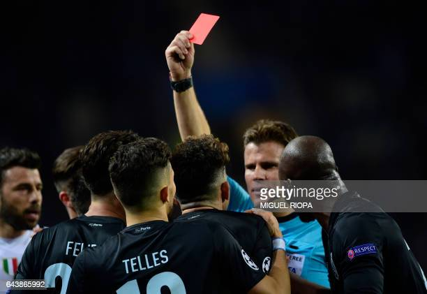 German referee Felix Brych shows red card to Porto's Brazilian defender Alex Telles during the UEFA Champions League round of 16 second leg football...