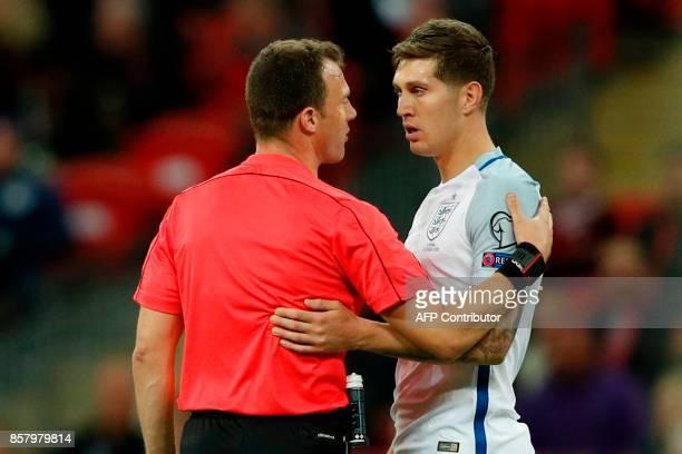 German referee Felix Zwayer talks with England's defender John Stones after pushed over Slovenia's defender Bostjan Cesar in an off the ball incident...