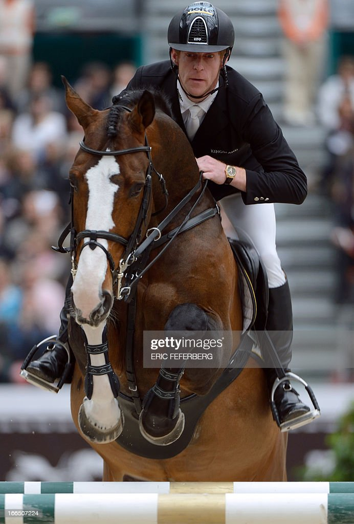 German rider Marcus Ehning and his horse Plot Blue jump during the Hermes Jumping competition at the Grand Palais in Paris on April, 2013. Ehning won the Saut Hermes CSI 5* class 6 with French rider Penelope Leprevost . AFP PHOTO / ERIC FEFERBERG.