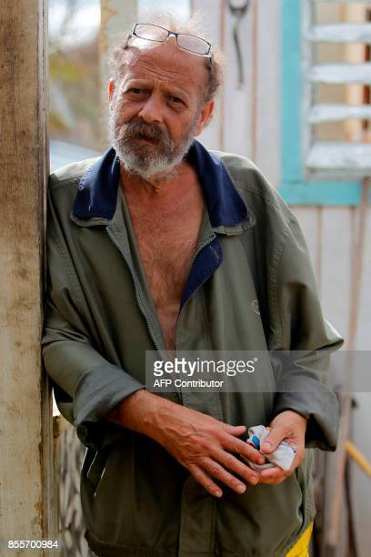 German Rodriguez poses for a picture from inside his destroyed house by Hurricane Maria in Aibonito central Puerto Rico on September 29 2017 German...