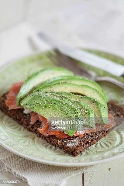 German rye bread with salmon and avocado slices on a plate