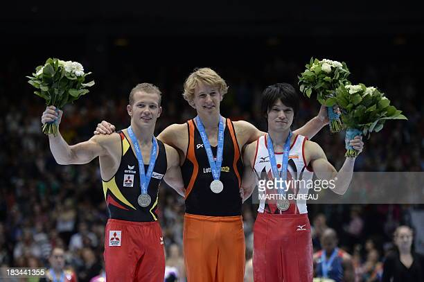 German silver medalist Fabian Hambuechen Dutch gold medalist Epke Zonderland and Japanese bronze medalist Kohei Uchimura celebrate during the podium...