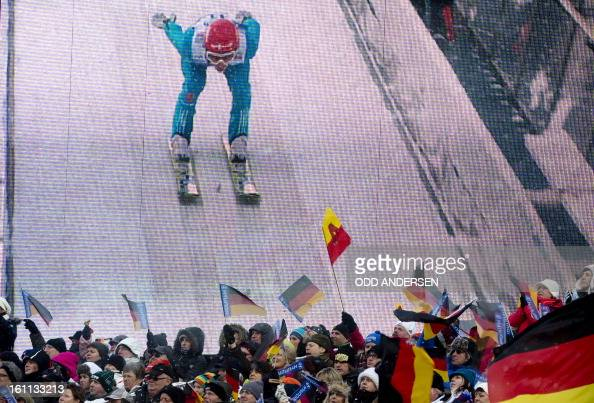 German ski jump enthusiasts wave their flags in front of a giant screen with home athlete Richard Freitag of Germany coming down the jump during the...