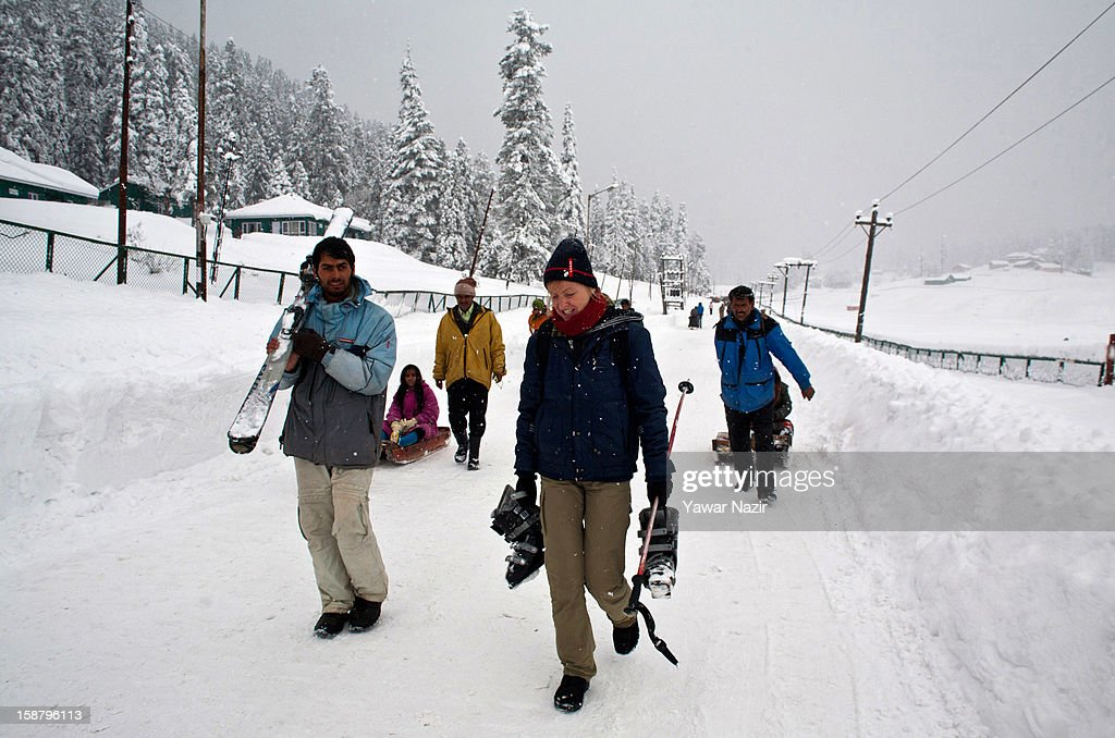 A German skier walks towards the slopes during a snowfall on December 29, 2012 in Gulmarg, 54 km (35 miles) to the west of Srinagar, the summer capital of Indian-administered Kashmir, India. With the second round of heavy snowfall in Kashmir valley, skiers from around the globe have descended on the ski resort of Gulmarg, known for long-run skiing, snow-boarding, heli-skiing and steep mountains. Gulmarg is located less than six miles from the ceasefire line or Line of Control (LoC) that divides Kashmir between India and Pakistan. As a sense of normalcy has started to return to this strife-torn region, various foreign governments, including the United Kingdom, have lifted the travel advisory to its citizens traveling to Kashmir, raising the hopes of the local tourism industry, officials said.