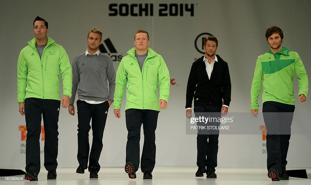 German snowboarder Patrick Bussler (L) biathlete Florian Graf (C) and Konstantin Schad (R) present along with models the official German olympic team's outfit for the next Olympic wintergames in Sochi, during a fashion show at the Duesseldorf fair ground, western Germany, on October 1, 2013. STOLLARZ