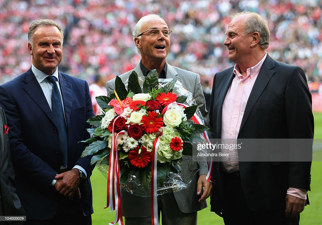 German soccer legend <a gi-track='captionPersonalityLinkClicked' href=/galleries/search?phrase=Franz+Beckenbauer&family=editorial&specificpeople=210545 ng-click='$event.stopPropagation()'>Franz Beckenbauer</a> (C) sings as <a gi-track='captionPersonalityLinkClicked' href=/galleries/search?phrase=Karl-Heinz+Rummenigge&family=editorial&specificpeople=634867 ng-click='$event.stopPropagation()'>Karl-Heinz Rummenigge</a> (L) and the president of Bayern Muenchen <a gi-track='captionPersonalityLinkClicked' href=/galleries/search?phrase=Uli+Hoeness&family=editorial&specificpeople=634868 ng-click='$event.stopPropagation()'>Uli Hoeness</a> (R) smile before the Bundesliga match between FC Bayern Muenchen and SV Werder Bremen at Allianz Arena on September 11, 2010 in Munich, Germany.