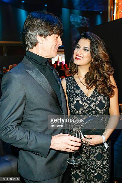 German soccer trainer Joachim Loew and Miss Bambi Rumi Akaber pose at the Bambi Awards 2016 party at Atrium Tower on November 17 2016 in Berlin...
