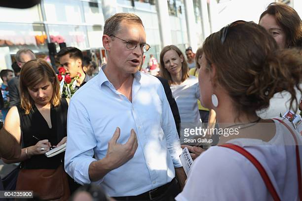 German Social Democrat and current Berlin Mayor Michael Mueller speaks to passersby as he campaigns in Berlin state elections at the Gesundbrunnen...