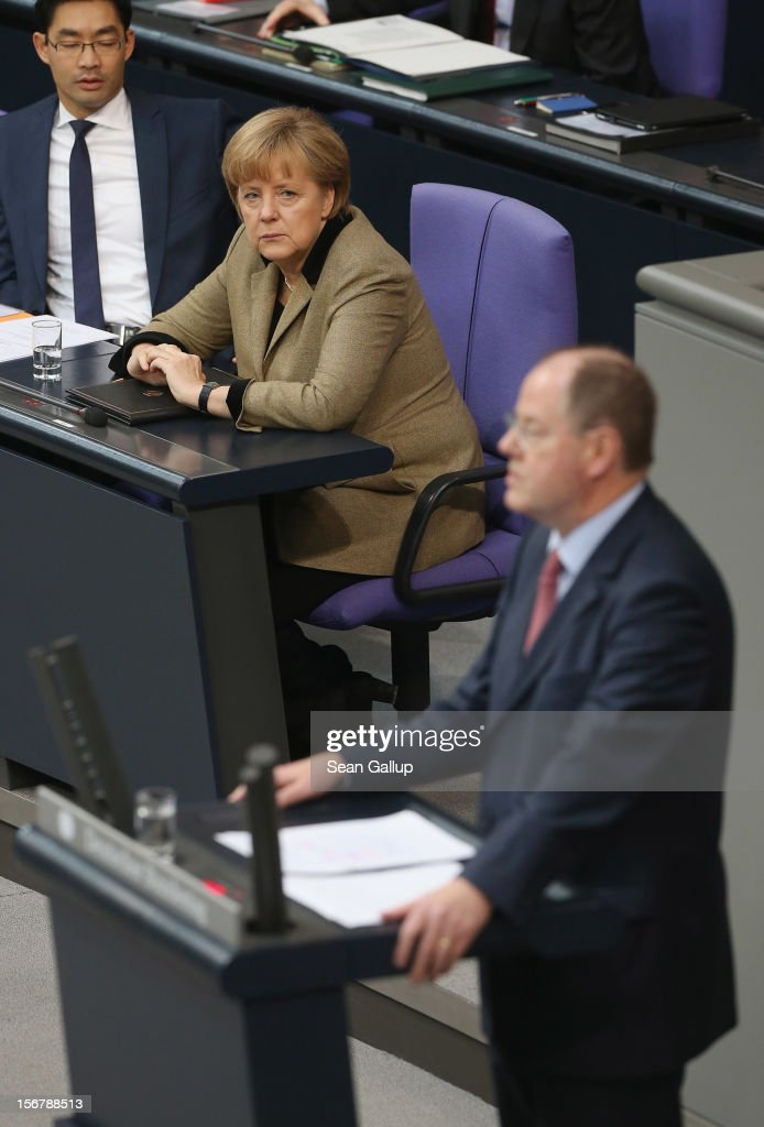 German Social Democrat (SPD) chancellor candidate Peer Steinbrueck speaks during debates at the Bundestag over the 2013 federal budget as German Chancellor <a gi-track='captionPersonalityLinkClicked' href=/galleries/search?phrase=Angela+Merkel&family=editorial&specificpeople=202161 ng-click='$event.stopPropagation()'>Angela Merkel</a> sits nearby on November 21, 2012 in Berlin, Germany. Bundestag members are debating the budget over four days this week.