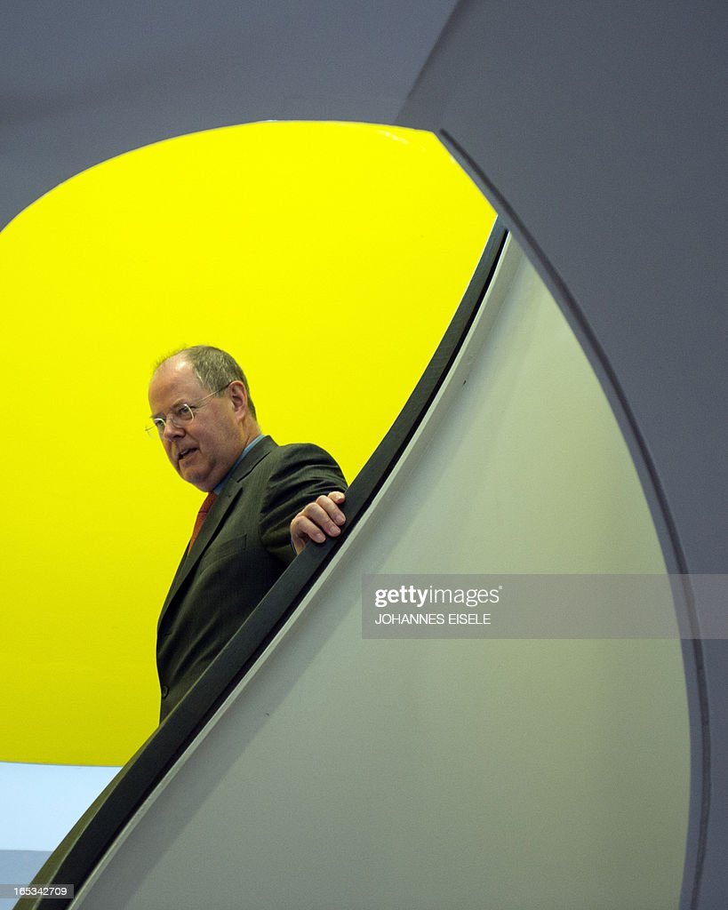 German Social Democratic Party (SPD) chancellor candidate Peer Steinbrueck walks down stairs at the Universal building in Berlin on April 3, 2013. Steinbrueck visited various firms including Universal Music Group International as part of his regional tour in this general election year.