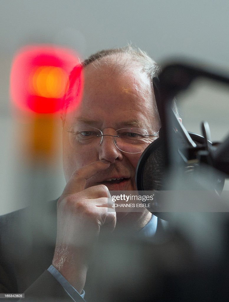 German Social Democratic Party (SPD) chancellor candidate Peer Steinbrueck is interviewed in a radio station in Berlin on April 3, 2013. Steinbrueck visited various firms including Universal Music Group International as part of his regional tour in this general election year. AFP PHOTO / JOHANNES EISELE