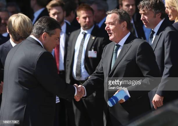 German Social Democrats Chairman Sigmar Gabriel greets former German Chancellor Gerhard Schroeder as Schroeder arrives at the 150th anniversary...