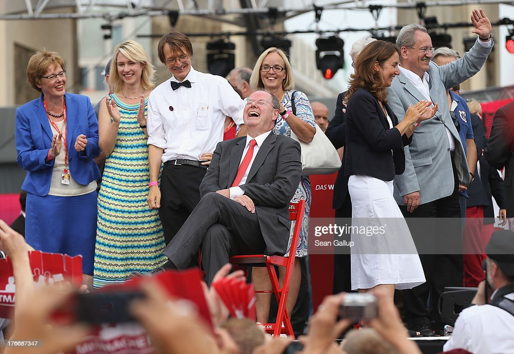German Social Democrats (SPD) chancellor candidate <a gi-track='captionPersonalityLinkClicked' href=/galleries/search?phrase=Peer+Steinbrueck&family=editorial&specificpeople=209110 ng-click='$event.stopPropagation()'>Peer Steinbrueck</a> (seated) laughs on stage with other leading party members, including <a gi-track='captionPersonalityLinkClicked' href=/galleries/search?phrase=Manuela+Schwesig&family=editorial&specificpeople=6048691 ng-click='$event.stopPropagation()'>Manuela Schwesig</a> (L, in stripes) and Munich Mayor <a gi-track='captionPersonalityLinkClicked' href=/galleries/search?phrase=Christian+Ude&family=editorial&specificpeople=729442 ng-click='$event.stopPropagation()'>Christian Ude</a> (R, waving) after speaking at the 'Deutschland Fest' marking the 150th anniversary of the SPD on August 17, 2013 in Berlin, Germany. Stenbrueck is trailing incumbent Chancellor Angela Merkel and the German Christian Democrats (CDU) significantly ahead of federal elections scheuled for September 22.
