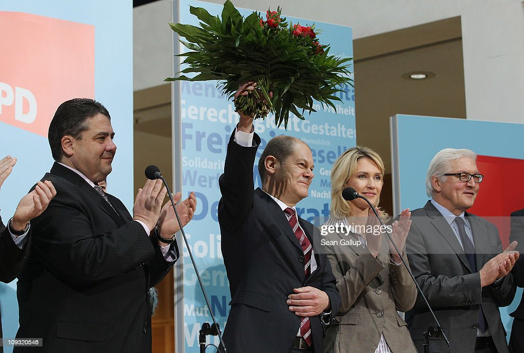 German Social Democrats (SPD) Hamburg mayoral candidate Olaf Scholz (C) holds up flowers at SPD headquarters as party Chairman Sigmar Gabriel (L), party board member Manuela Schwesig and SPD Bundestag faction leader Frank-Walter Steinmeier (R) look on following Scholz's election victory the day before on February 21, 2011 in Berlin, Germany. The SPD took 48.3% of the vote and trounced the incumbent German Christian Democrats (CDU), the party of German Chancellor Angela Merkel, in what is the worst state election-to-election loss of any German political party's history. The election is a severe setback for Merkel, whose party faces another six German state elections this year.