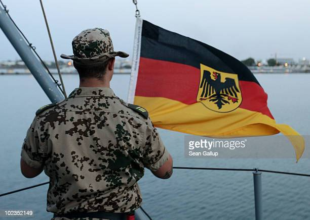 German soldier participating in the international ATALANTA antipirate campaign lowers the German flag on board the German naval frigate...