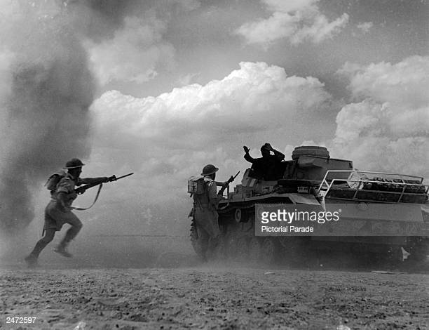 A German soldier surrenders as the British infantry rushes his tank Africa WWII circa 1942